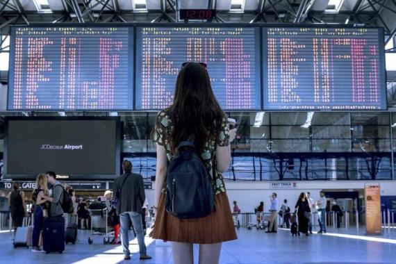 Joven en el aeropuerto buscando vuelo