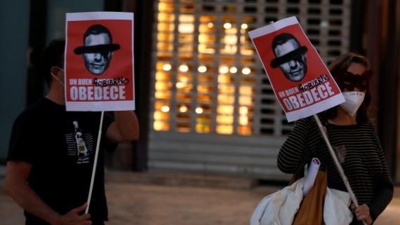 Manifestantes en Málaga llevan los carteles que vende Gobierno Dimisión.