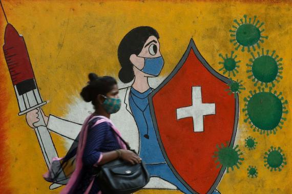 Una mujer camina delante de un mural sobre el coronavirus en Mumbai