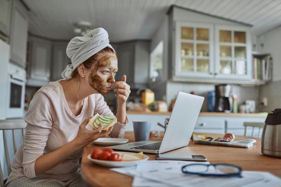Una mujer come sano delante del ordenador con una mascarilla puesta.