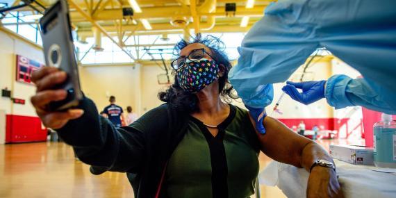 Una mujer se hace un selfie mientras recibe una vacuna