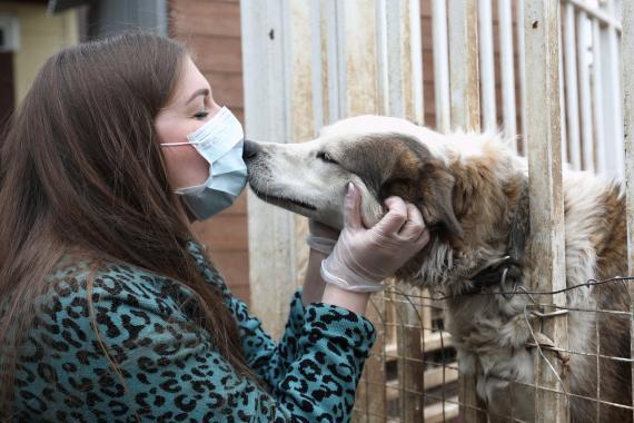 Una mujer con mascarilla besa a un perro
