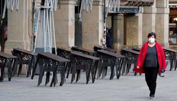 Una mujer con mascarilla pasa ante la terraza de un bar cerrado en Pamplona