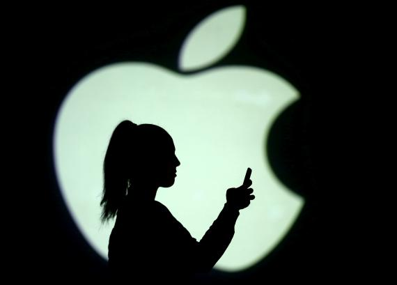 Una mujer utiliza un teléfono móvil delante de un logotipo de Apple