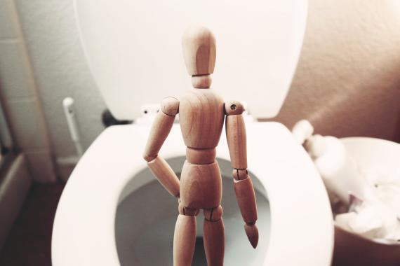 Un muñeco de madera hace sus necesidades en el inodoro.