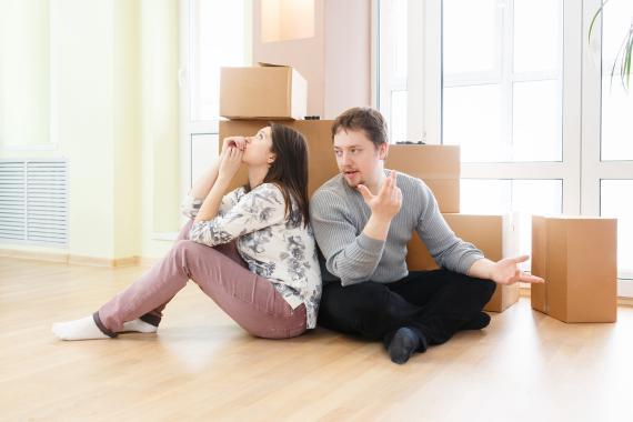 Una pareja sentada en el suelo con cajas alrededor.