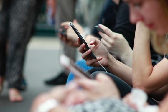 Varias personas miran el móvil en el metro.