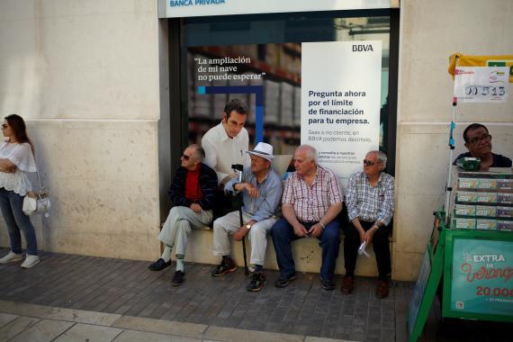 Pensionistas sentados enfrente de una sede del BBVA.