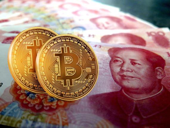 Un billete de curso legal en China junto a dos bitcoins.