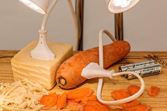 Un cable enchufado en una zanahoria y un queso.