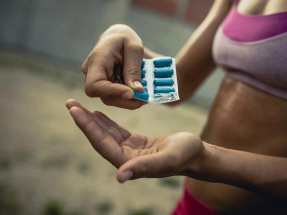 close-up image of a person in a sports bra taking supplement pills