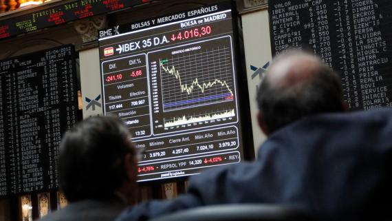 Dos traders observan la marcha de la cotización del Ibex 35 en la Bolsa de Madrid