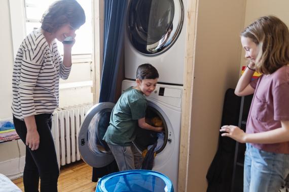 Familia poniendo la lavadora en casa