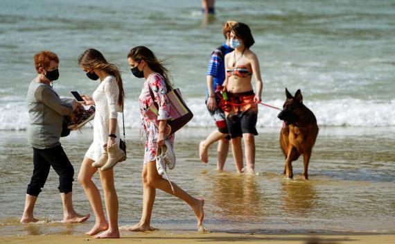 Gente pasea por la playa en medio de la pandemia en España.