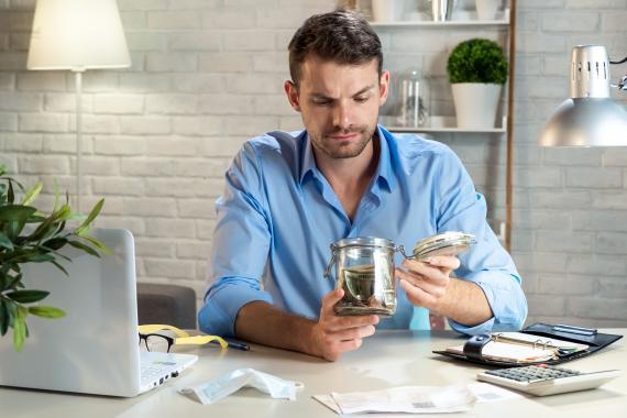 Hombre ahorrando dinero en un tarro