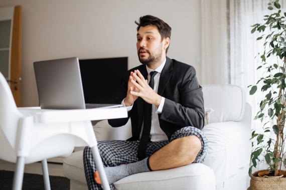 Un hombre con americana, corbata y pantalón de pijama delante del ordenador.