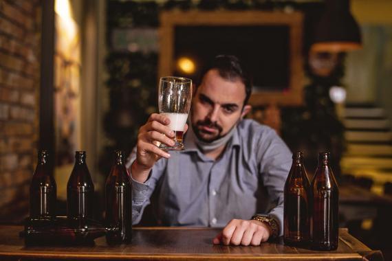 Hombre bebiendo una caña en un bar