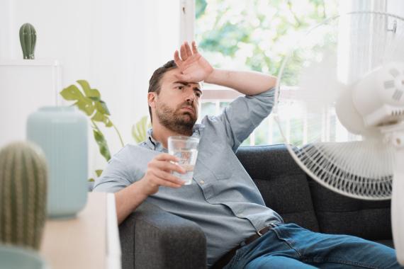 Un hombre trata de refrescarse con un vaso de agua y un ventilador.