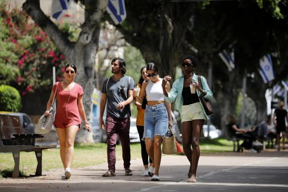 Pedestrians walk on a boulevard in Tel Aviv on April 18, 2021.