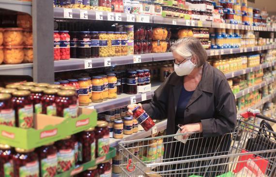mujer comprando en el supermercado productos procesados