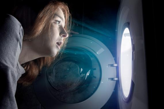 Una mujer mira en el interior de la lavadora.