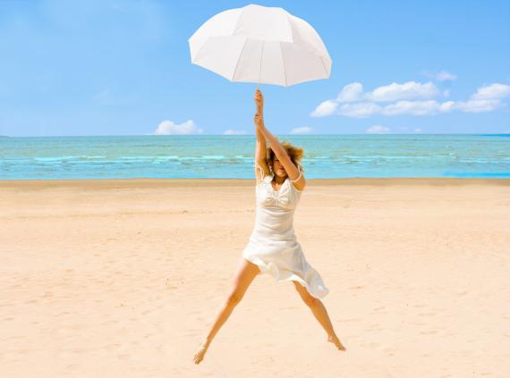 Una mujer sale volando agarrada a un paraguas en la playa.