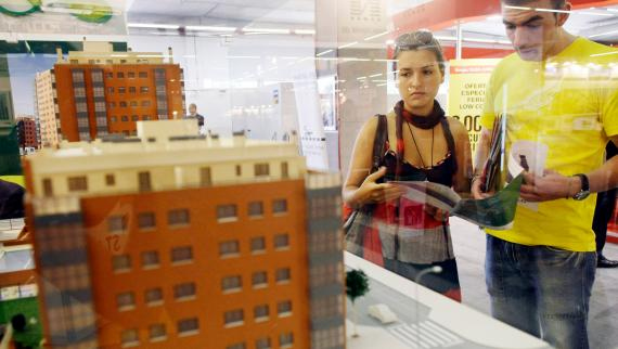 Una pareja observa la maqueta de un bloque de edificios en una feria de vivienda. Reuters
