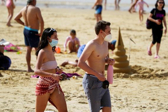 Una pareja paseando por la playa con mascarilla