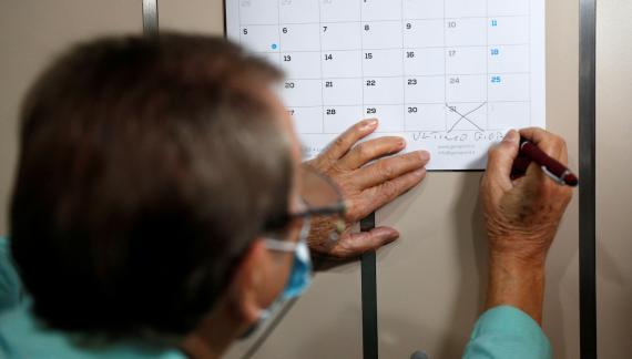 Un peluquero con mascarilla marca en el calendario la fecha de su jubilación