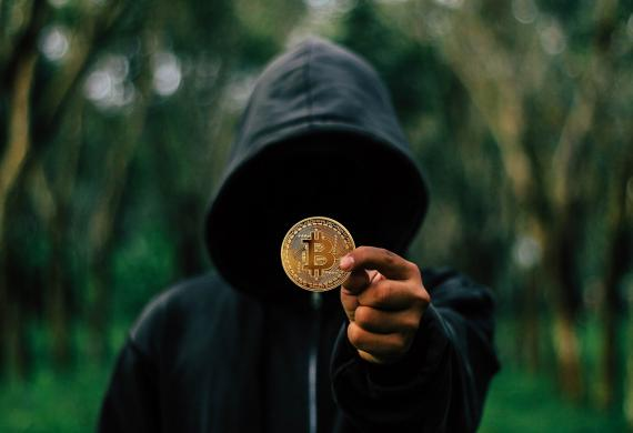 Una persona con la cara oculta muestra un bitcoin.