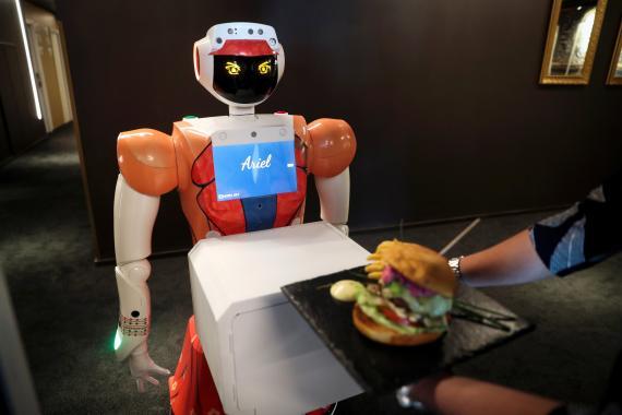 Un robot camarero lleva una hamburguesa
