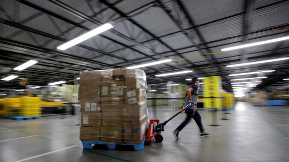 Un trabajador de Amazon corriendo por uno de sus almacenes.