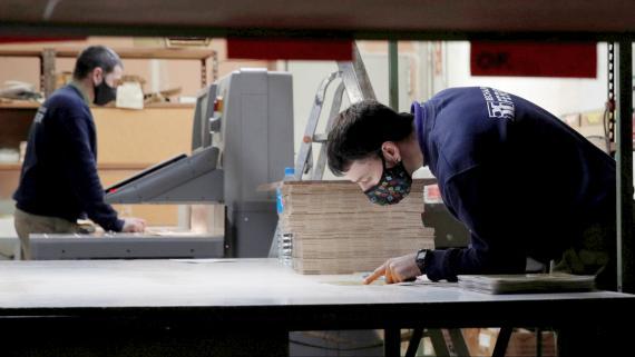 Trabajadores con mascarilla en una fábrica de tableros de ajedrez en Barcelona