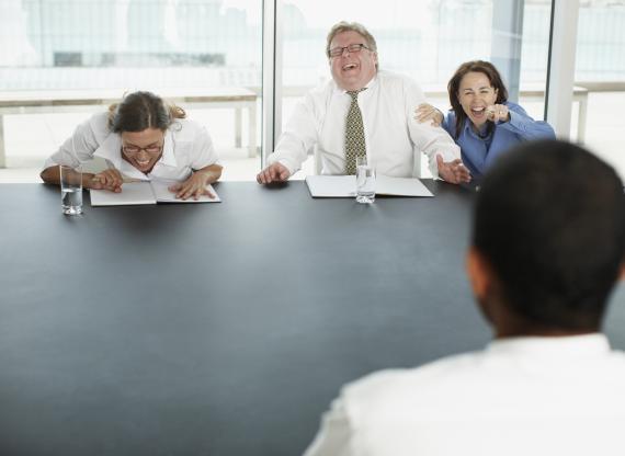 Tres reclutadores se ríen del candidato en una entrevista de trabajo.
