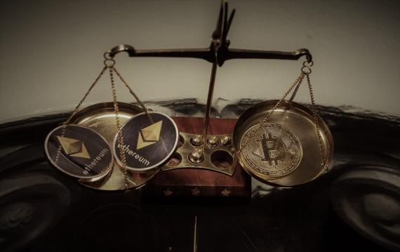 2 monedas de ethereum y una de bitcoin en una balanza.