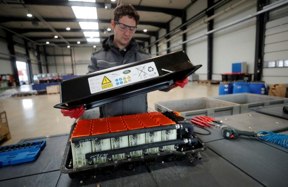 Un operario desmonta una batería de litio de vehículo usada en una fábrica alemana.