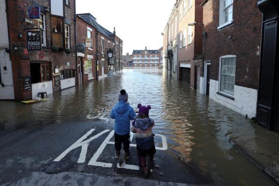 Dos niños parados en una calle parcialmente inundada después de que el río Ouse se desborde en York (Gran Bretaña).