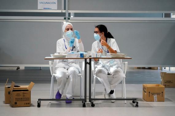 Dos enfermeras preparando una dosis de la vacuna contra el COVID-19