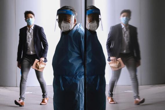 Un hombre hace guardia después de que HSBC cerrase su sede debido a múltiples casos de COVID-19