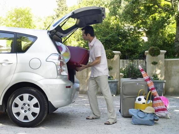 Un hombre metiendo las maletas en el coche