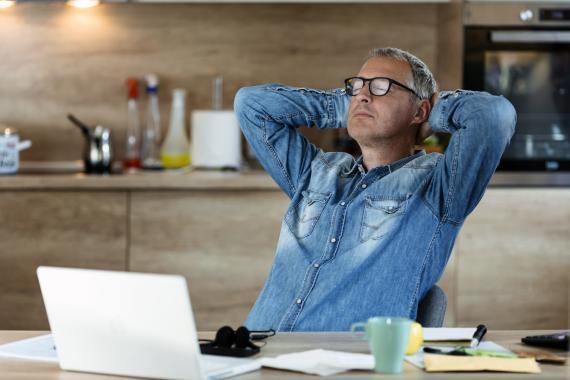 Un hombre relajado sentado en el ordenador trabajando.