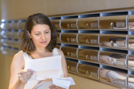 Una mujer mirando las cartas en el buzón