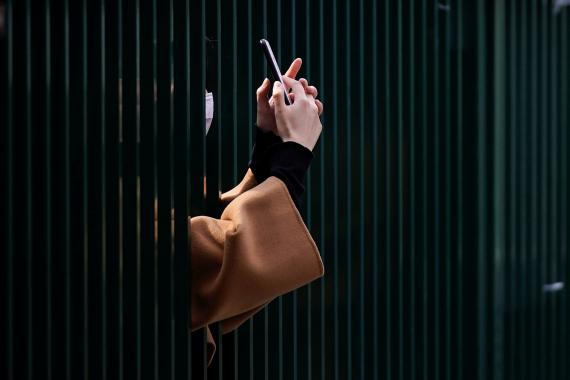 Mujer sujeta un móvil entre barrotes.