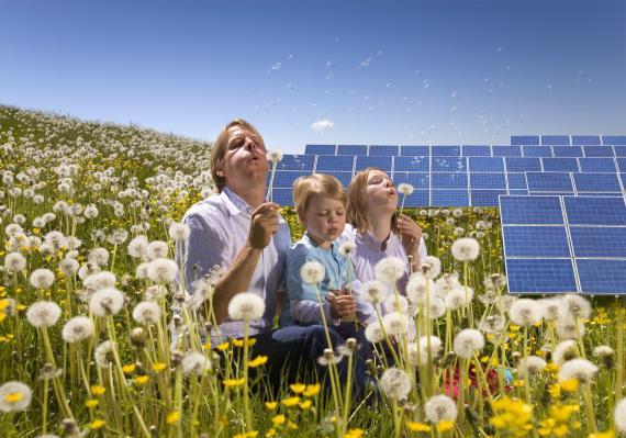Un padre, su hija y su hijo junto a una instalación de placas solares.