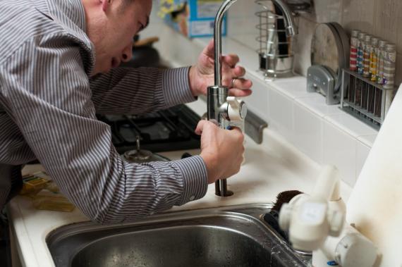 Una persona trata de arreglar un grifo.