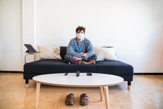 Un chico enfermo sentado en el sofá.