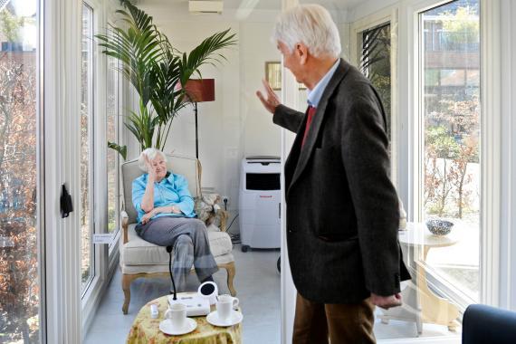 Un hombre visita a su esposa en un centro de atención para personas mayores con demencia, en una casa de cristal por el COVID-19.