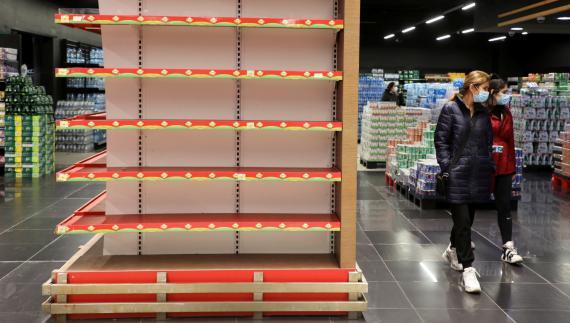 Dos mujeres pasean por un supermercado con las estanterías vacías durante la pandemia de coronavirus