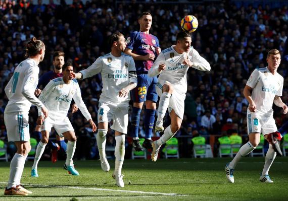 Futbolistas del Real Madrid y del FC Barcelona disputan un balón de cabeza.