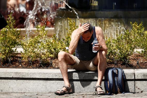 Un hombre se echa agua en la cabeza por el calor, en España.